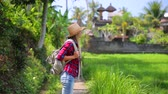 Beautiful girl traveling with backpack, slow motion, wearing straw hat, standing and looking around, enjoying beautiful nature of Asia. Full HD Video 1920x1080 Wideo
