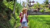 Traveler woman with backpack walking in the fresh green tropical park, active lifestyle, happy summer vacation in Asia. Full HD Video 1920x1080