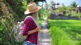 Beautiful girl traveling with backpack, wearing straw hat, standing and looking around, enjoying beautiful nature of Asia. Full HD Video 1920x1080