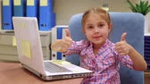 Cute little girl playing on the laptop at home, gesturing happiness by thumbs up, enjoying modern technology for game and education.
