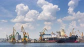 industrial : Constanta, Romania - May 27, 2014: Time lapse with cumulus clouds and large cargo boats docked for shipping in the industrial seaport of Constanta, the largest on the Black Sea and the 18th in Europe.