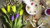 müsli : Breakfast granola, muesli with flowers tulips, rustic style, top view, slow motion