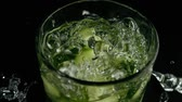 finely : Finely chopped on quarters cucumber falls into a glass with ice water with large sprays. Slow mo