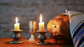 csészealj : Shabbat candles in glass candlesticks with blurred covered challah Stock mozgókép