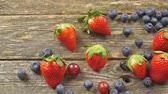 table grapes : summer fruits on a wooden table. Blueberries Grape Strawberries SLOW MOTION hd video Stock Footage