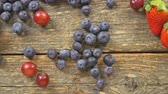 table grapes : Blueberries Grape Strawberries on a wooden background SLOW MOTION hd video