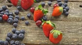 amoras : ingredients for a healthy Grape Strawberry Blueberries berries, fruit, and wooden background, top view, horizontal SLOW MOTION hd video
