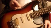 Guitarist. Close-up on a male hand starting playing electric guitar. Blurry amplifier  speaker box in background. Stock Footage
