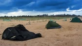 two broken camping tents at stormy weather and good tent at back Stock Footage