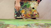 abstrakcja : A woman paints a landscape with oil paints with a palette and brush. Top view