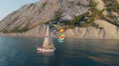 Aerial shooting of a sailing yacht in the sea. Sunny day at sea. Man sailing on yacht at the sea.