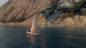 A white yacht under a black and white sail with a crew sails calmly along the blue sea along a mountainous shore. Vídeos