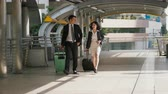 The businessman and pretty businesswoman walking and talking together, They are dragging a baggage with wheel along the passageway, feel happy