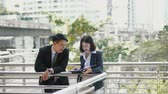 Zoom in shot to two colleague were standing on the bridge and view the documents in the file, outside the office working, co-worker concept Stock Footage