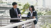 Zoom in shot to Male and female Asian co-workers look over data on a document in the file and talking together on the bridge,  outside the office working, co-worker concept