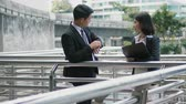 Dolly shot two Asian colleagues were standing and male checking time with wristwatch on the bridge,  and looking at the sky train  through Skyscraper, Then ask a female worker walked out