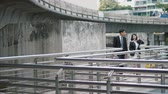 Two Asian colleagues carry bag  and holding the document file and walk up the bridge to go to the nearest sky train station. man watch wristwatch, and the Sky train runs through Skyscraper Stock Footage