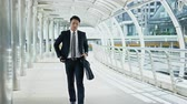 Dolly shot scene Young businessman hold a briefcase, watch wristwatch and stopping to pick up the smartphone on walkway on bridge Stock Footage