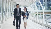 The businessman and pretty businesswoman walking and talking together, checking map in smartphone and walk through the camera Stock Footage
