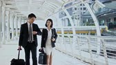 The businessman and pretty businesswoman walking and talking together and walk through the camera Stock Footage