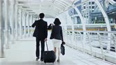 Dolly shot with behind of the businessman dragging a baggage and pretty businesswoman hold briefcase, they are walking and talking together Stock Footage