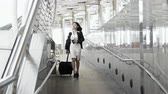 Locked shot with young woman walks along a baggage with haste, stopping to read the label. before moving on with hastiness through the camera, back of businessman walk going in the opposite direction