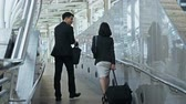 Dolly shot with behind of the businessman hold briefcase  and pretty businesswoman dragging a baggage, they are walking and talking together Stock Footage