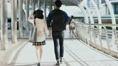 Medium Long shot and tracking or pan camera with behind of the young couple walking holding hands, talk sweetly and walking together Stock Footage