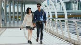 Tracking or pan camera with the young couple walking holding hands, talk sweetly and walking together in city Stock Footage