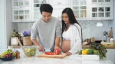 sweet pepper : Young pregnant use knife to slicing red sweet pepper,  husband help her slice and put into glass of vegetables salad and mix them