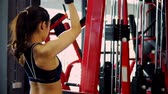 Locked and Close up shot with back of strong woman lifting weights on fitness exercise equipment in fitness gym, healthy concept