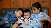 figyelem : Fixed shot with three children are watching video from smartphone on the couch in living room together Stock mozgókép