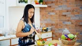 spouses : Young woman cooking salad vegetable in glass bowl in modern kitchen