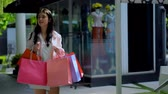 vela : Young pretty woman holding shopping bags come in with pleasure and excitement when her see something and walk out Vídeos