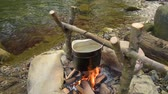 tea pot : Cooking food in pot over campfire