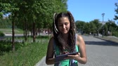 videochat : Attractive girl walks in the park using a tablet