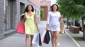 paper bag : Two beautiful girlfriends carry packages of different colors with shopping after shopping. slow motion. HD