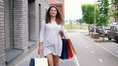 farra : A girl in a light dress goes down the street after shopping and carries packages with purchases in her hands. slow motion. HD