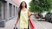 farra : A young girl in a long yellow dress goes around the city after shopping having a good mood. 4K