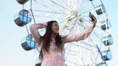 hk : A young girl with long hair in a long dress makes selfie using a smartphone standing near the Ferris wheel. slow motion.