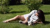 front or back yard : Young girl with a dog in the park on the grass.slow motion. Stock Footage