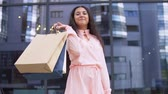 farra : Young girl in a dress after shopping with packages in hands is happy with purchases. slow motion. Vídeos