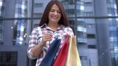family business : Young girl after shopping with packages in hands having a good mood. slow motion.