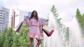paper bag : A girl near a fountain in the park after shopping with bags in hand. slow motion.