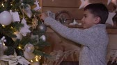 bombki : A little boy decorates a Christmas tree with a beautiful ball.HD