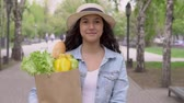 bagietka : A young beautiful woman in good mood walks down the street in a city park and carries a large grocery bag. Wideo