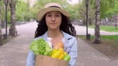 bagietka : A young attractive woman in a denim jacket and hat carries a grocery bag while having a good mood and is smiling. 4K