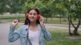 pillantás : Funny cheerful girl dancing in the park near the trees listening to cheerful music in headphones. Fun mood. Portrait