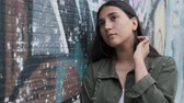 tonificado : pensive young girl stands near the wall with graffiti runs a hand through her hair and is sad leaning against the wall Stock Footage