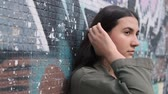 nőiesség : young beautiful thoughtful brunette girl stands near the wall with graffiti and runs her hand through her hair